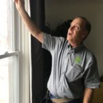 A man points to a source of air leakage in a window
