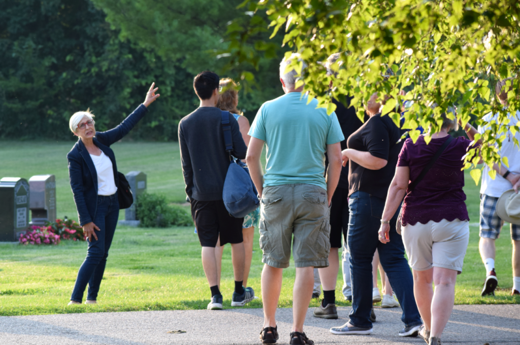 A woman motions to a tree and speaks to a group of people.