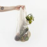 A hand holds out a mesh bag of produce