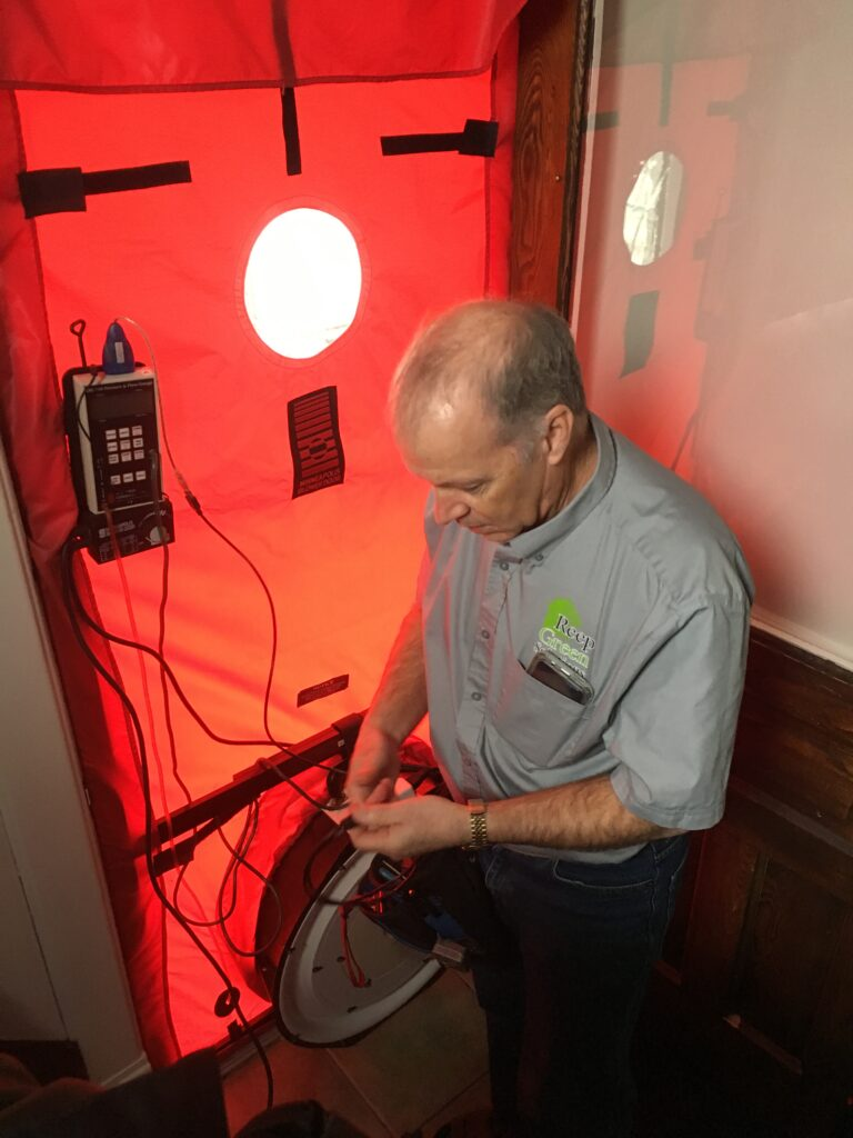 A man connects wires to a blower door device.