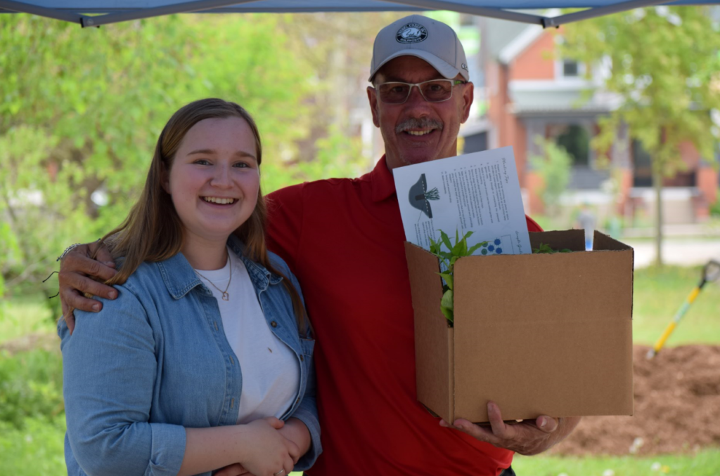 A man with his arm around a woman holds a box of plants and planting instructions.