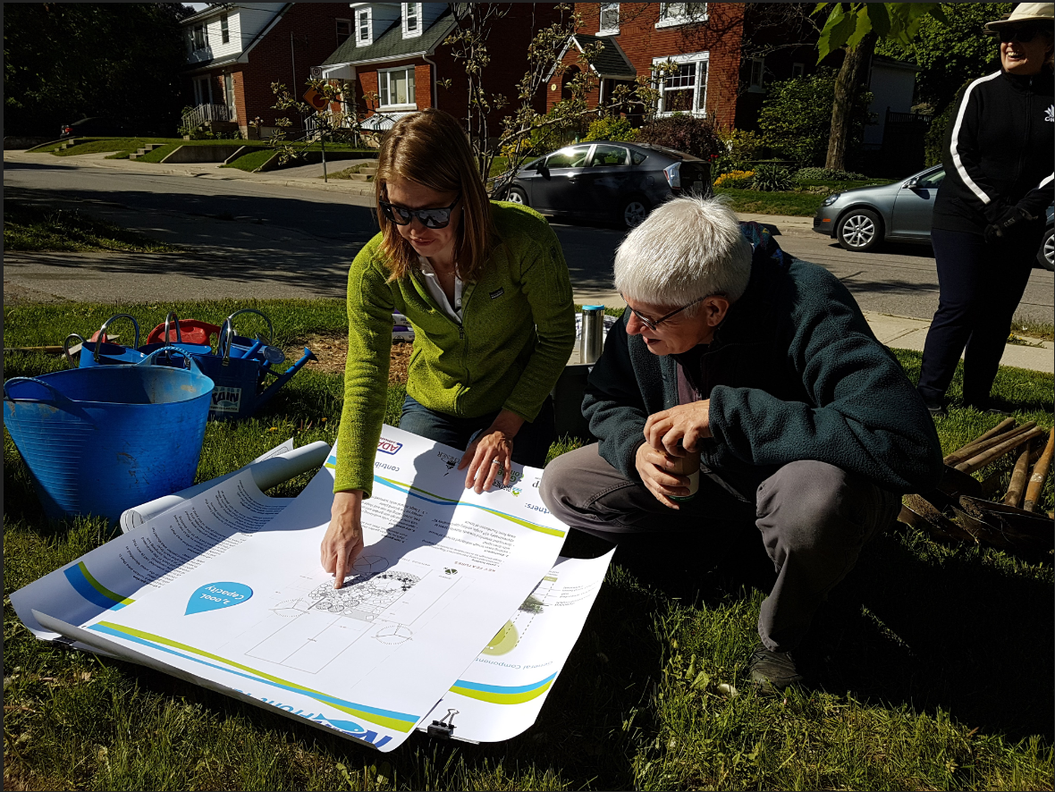 rain garden coach becca showing a homeowner paper maps and plans outside on the grass