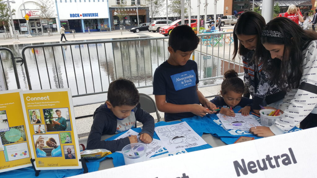 5 Kids working on anactivity on a table at the project neutral booth.