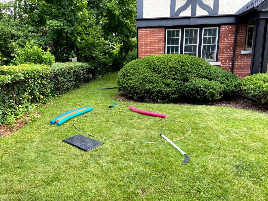 various tools and hoses laid on top of grass to begin planning location of rain garden