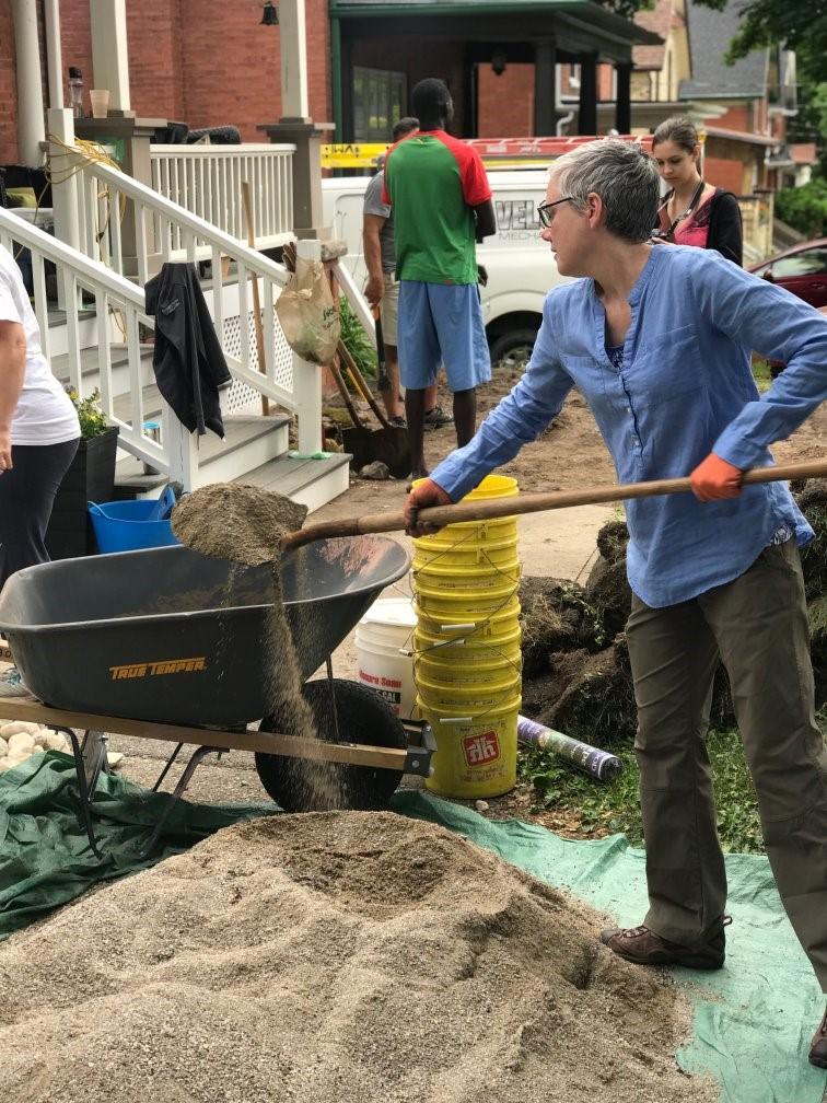 woman shovel rocks out of a wheelbarrow for rain garden