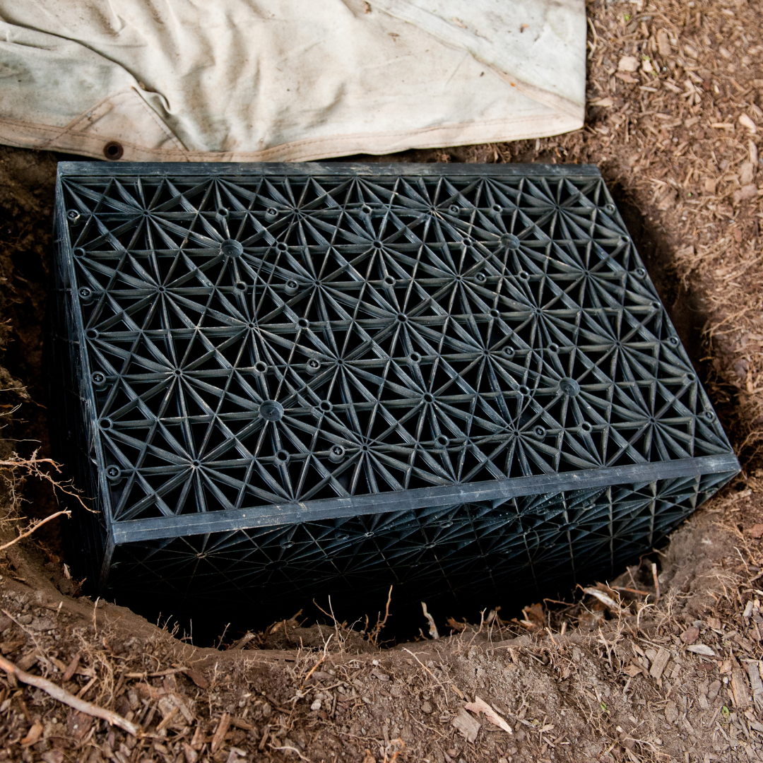 A black plastic cube inserted into the ground to assist in water infiltration.