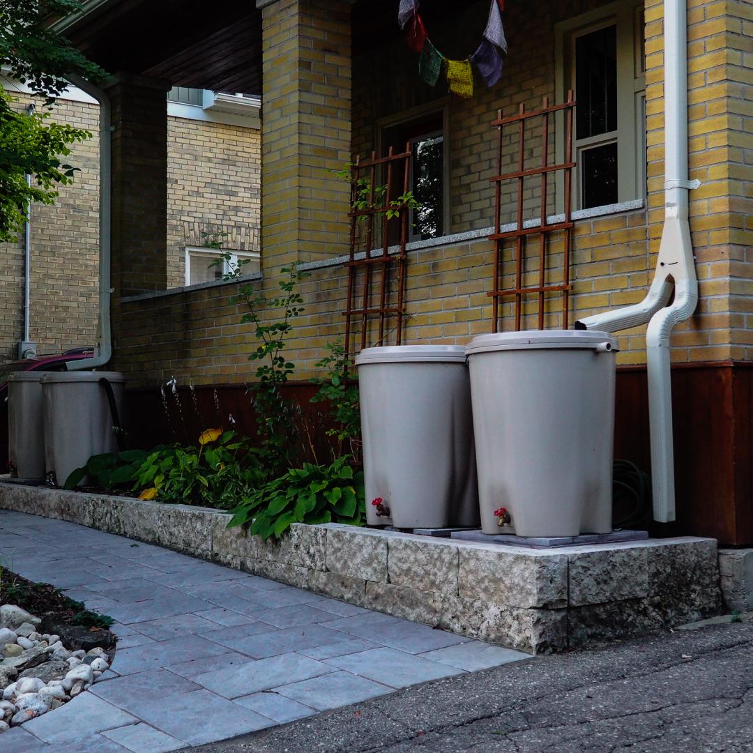 Two rain barrels outside of a tan brick house.