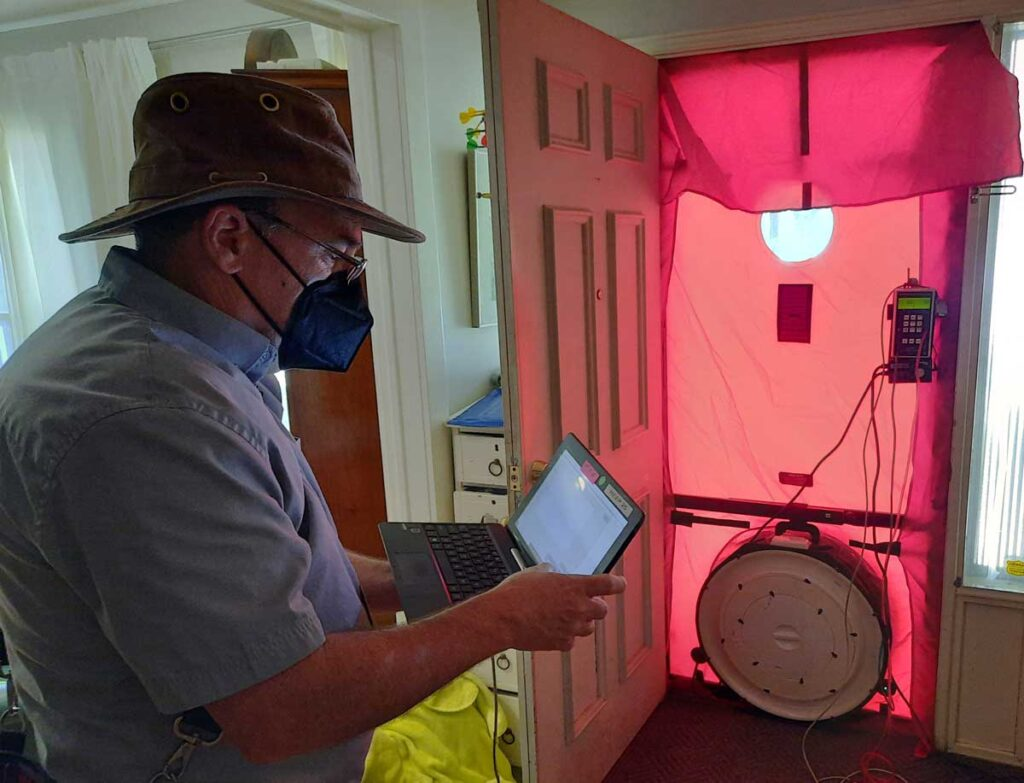 A man operates a computer connected to a blower door device