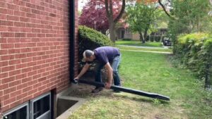 A man is removing a downspout