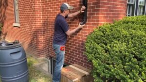 A man fits an elbow onto a downspout