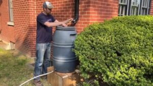 A man measures the distance between a rain barrel and downspout